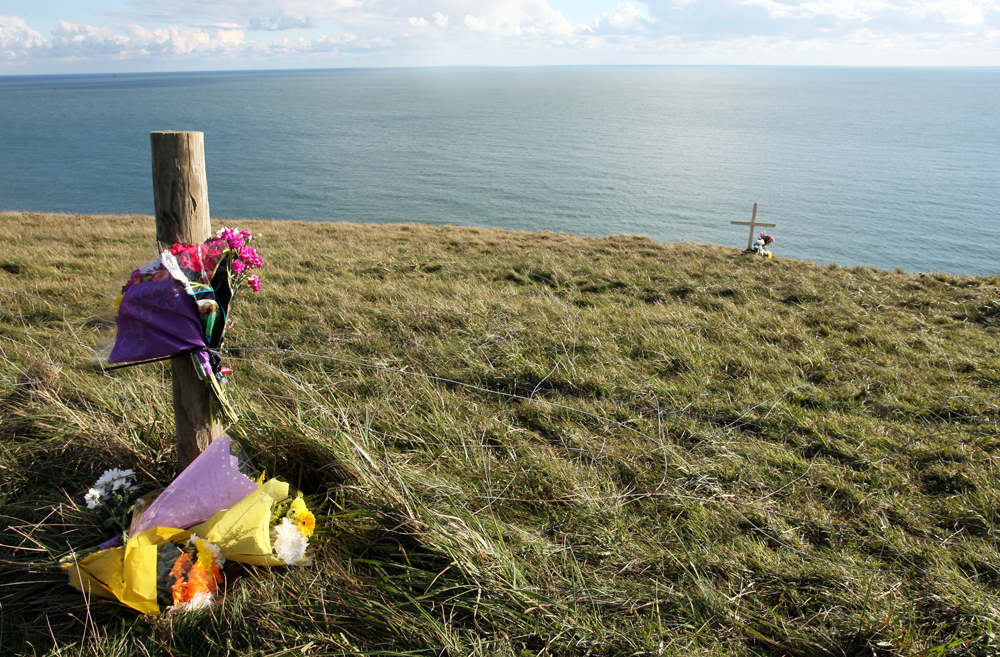 13-12-2012 - SANDOWN, ISLE OF WIGHT - Floral tributes are left alongside a cross at the scene on Culver Downs were 20-year-old Robert Hayball took his own life after driving off the cliff edge before plummeting to the rocks and ocean below.